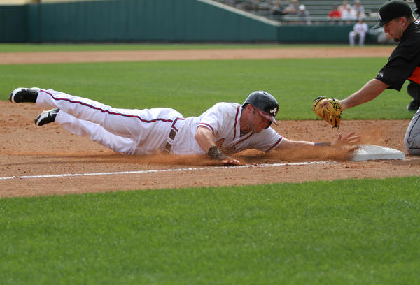 Atlanta Braves' Tyler Pastornicky slides safely into third beating the tag by Miami Marlins' third baseman Zack Cox during the fifth inning of their Grapefruit League Spring Training game at Walt Disney World's Champion Stadium in Lake Buena Vista, Fla.