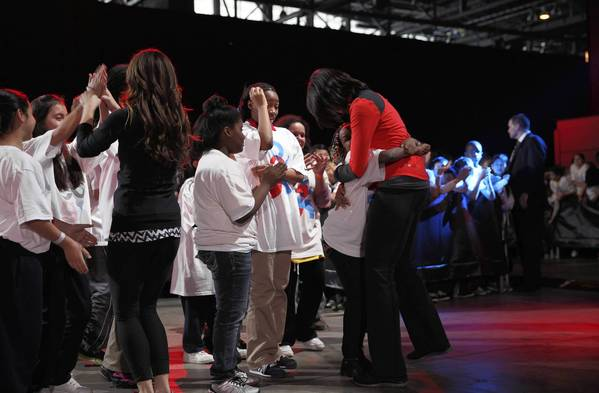 A girl gets a hug from Michelle Obama before some group dancing.