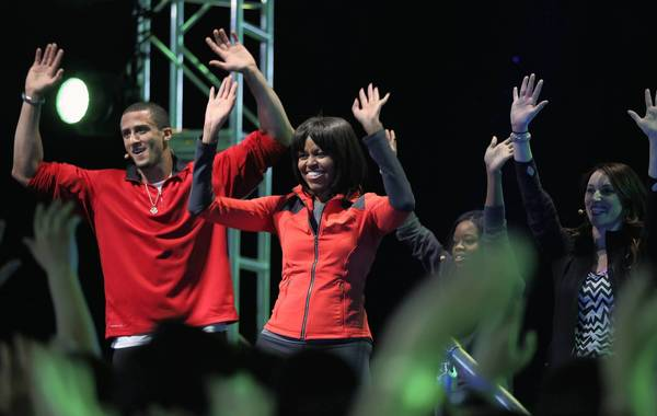 San Francisco 49ers quarterback Colin Kaepernick, left, and Olympic gold medal gymnast Gabby Douglas, second right, join Michelle Obama in an exercise routine.