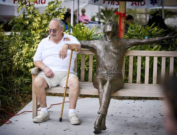 Fred Frascona takes a break next to a sculpture of John Lennon at the 36th annual Mount Dora Arts Festival.