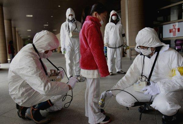 A young evacuee is screened at a shelter for radiation after a nuclear plant was damaged in Fukushima, Japan.