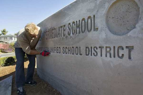 Gene Goble, the owner of Letters and Logos Sign Company, Inc. from Lake Forest, prepares a concrete sign for paint at Ensign Intermediate School on Wednesday. The sign had to be replaced after the original was made with the name Ensign Middle School.