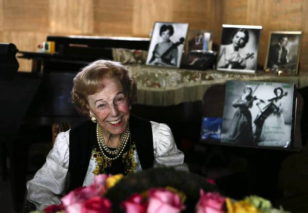 Violinist Alice Schoenfeld, who has taught at USC for more than 50 years, sits near portraits of herself and her late sister, Eleonore Schoenfeld, at her La Canada Flintridge home.