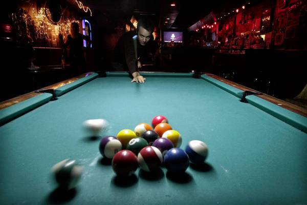 Jordan Lee shoots pool at the Smog Cutter in Los Angeles.