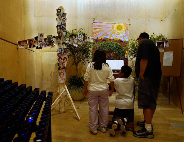 A family visits the chapel at the Cathedral of Our Lady of the Angels that Cardinal Roger Mahony dedicated to victims of clergy sexual abuse. Dozens of school photos have been left there by victims or their families.