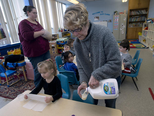 Afternoon Aftercare teacher Barbara McGunnigle pours a glass of milk for Khloe Ostfeld, 4, of Lower Macungie at the Allentown Jewish Community Center on Wednesday, February 27, 2013.  Built in 1958, the near-seven acre site on North 22nd St. has been put up for sale for an asking price of $6.9 million. The JCC's leadership is considering moving the facility to a location The JCC's leadership is considering moving the facility to a location west of Allentown.