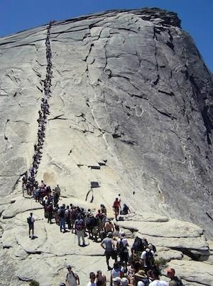 Tourists hike up the cables to the top of Half Dome in Yosemite National Park.