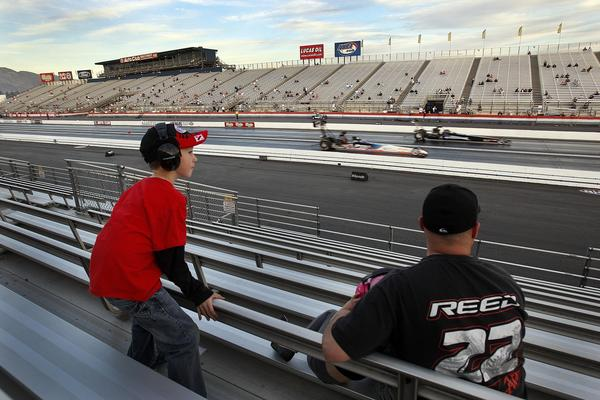 Steve Reed of San Bernardino and his son Jacob, 8, watch a qualifying drag race in the O'Reilly Auto Parts NHRA  Winternationals at the Auto Club Raceway at Pomona.