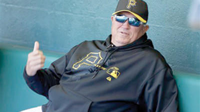 Pittsburgh Pirates manager Clint Hurdle sits in the dugout during an exhibition spring training baseball game Thursday against the Boston Red Sox in Bradenton, Fla.