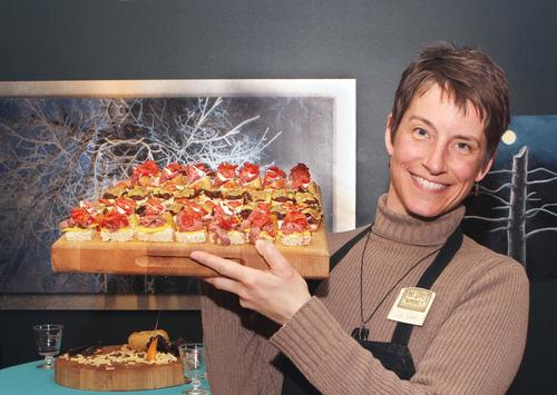 Caterer Liz Glass of Lake Street Market in Boyne City, marches in with another tray of flavorful hors d' oeuvres for guests of the Swirl Thursday at the Crooked Tree Art Center in Petoskey.
