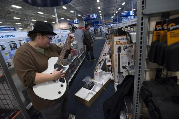 A shopper tries out a guitar at a Best Buy Co. store in San Francisco in January.