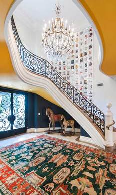 An ornate iron railing follows the staircase up to the second story.