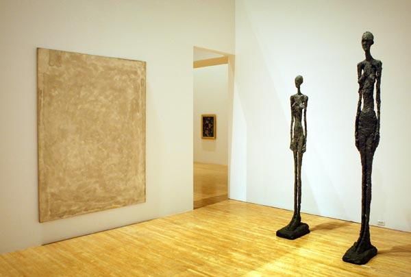 Alberto Giacometti statues tower over a room with a Sam Francis oil on canvas.