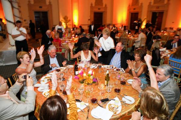 Attendess at last year's Boca Bacchanal cheer on a tablemate who just won an auction item.
