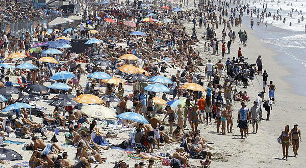 A survey conducted on behalf of the nonprofit Center for Biological Diversity finds that most registered voters in the United States believe that population growth is an important environmental issue. Here, crowds line the shoreline in Huntington Beach on a summer day.
