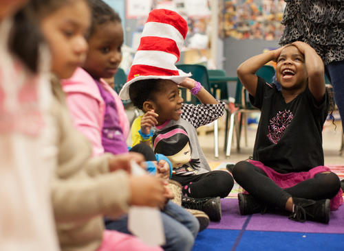 From right, Pre-K students Camille Smythe, and Zahara Torres (wearing hat), laugh as they pass the Seuss hat around the class during Read Across America day at Brock Bridge Elementary school.