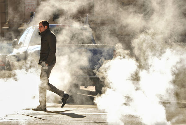 An unidentified man walks through billows of steam hitting the cold air on South Street and Redwood Streets. Temperatures dipped well below freezing, with highs only in the mid-20's.