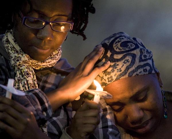 Dara-Lynn Baker, left, offers her shoulder as comfort to Tia Graham during a candlelight vigil for slain Coastal Carolina University student Anthony Liddell.
