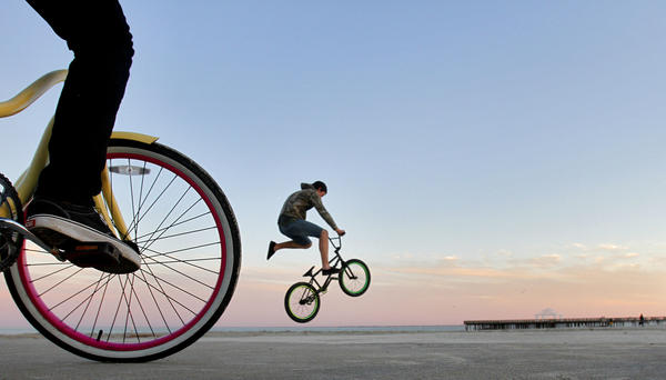 "Hunter Mallinson, 15, of Hampton practices bike tricks along the sea wall at Buckroe Beach Wednesday evening. <br /><br />  ""After spending most of the day confined to sitting in a chair while waiting for a car repairs, I embraced the opportunity to find a feature Wednesday afternoon. Having just moved to Newport News from Michigan less than two weeks ago, I set out to look in area that I hoped would give a few different possibilities. In Buckroe Beach, I found people walking in the sand, exercising, and finally a group of teenage boys riding their bicycles along the seawall. I laid on the ground next to a boy on his bicycle and waited for another boy to come into the frame while doing a trick."""