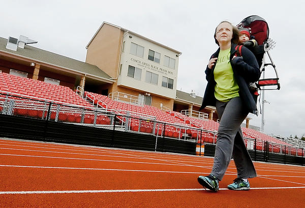 Tia Wright carries her son Colby on a walk around the North Hagerstown High School track Friday.  Wright is participating in the HEAL program that is preventing and reducing obesity in Washington County.