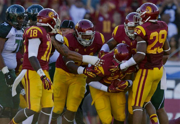 USC Trojans defensive tackle Christian Heyward (97) is swarmed by teammates after recovering a fumble against Hawaii.