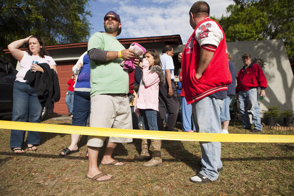 A crowd gathers at the home where a sinkhole opened up under a bedroom in Florida.