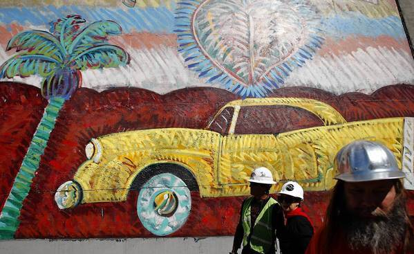 Willie Herron III, left, Mural Conservancy chief Isabel Rojas-Williams and street artist Risk in front of Frank Romero's work.