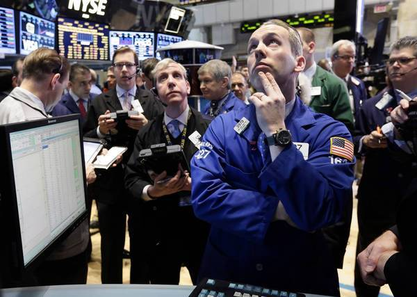 Specialist Patrick Kenny, foreground right, works on the floor of the New York Stock Exchange. The Dow rose 35 points but stopped short of a record with automatic government spending cuts about to kick in.