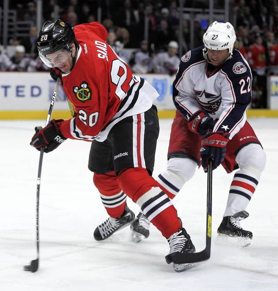 Brandon Saad shoots in front of the Blue Jackets' Vinny Prospal in the first period.