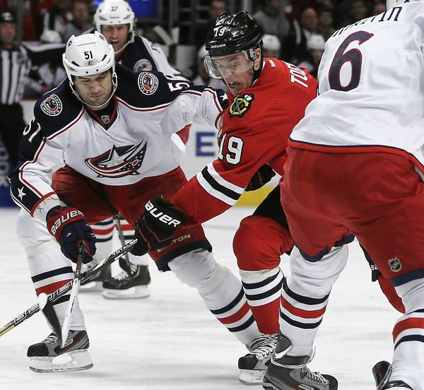 Jonathan Toews battles the Blue Jackets' Fedor Tyutin in the first period.