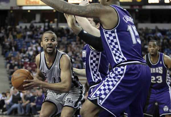 San Antonio Spurs point guard Tony Parker (9) controls the ball against Sacramento Kings point guard Jimmer Fredette (7) and center DeMarcus Cousins (15) during the fourth quarter at Sleep Train Arena. The San Antonio Spurs defeated the Sacramento Kings 108-102.