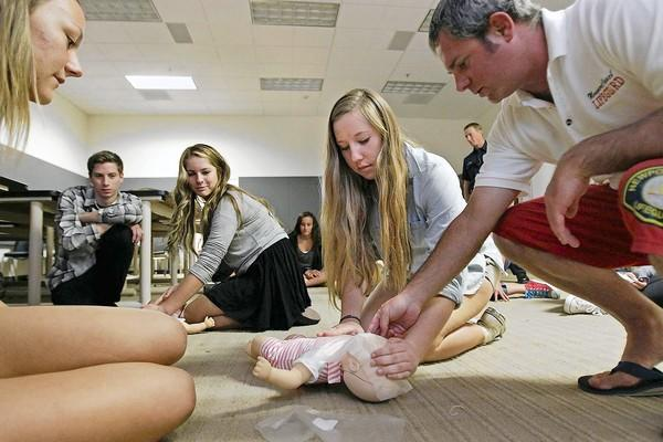 Newport Harbor High freshman Jordan Rausch, second from right, listens as Lifeguard 3 Rescue Boat Operator Brandon Hodding, right, instructs her during an Infant CPR & Choking class on Friday.