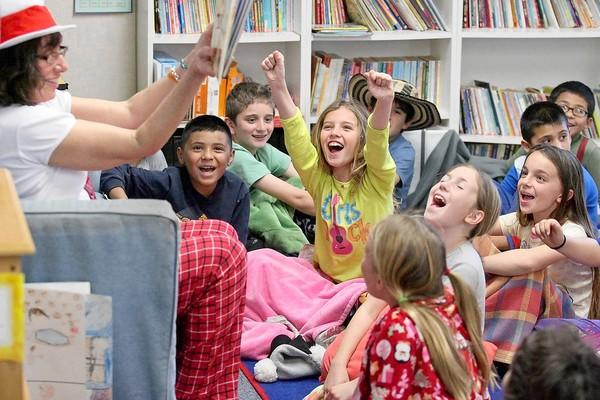 Third-grader Morgan Lamond, center, cheers after Principal Dr. Deborah Granger, left, finishes reading a Dr. Seuss story in celebration of Read Across America Day at Kaiser Elementary School on Friday.