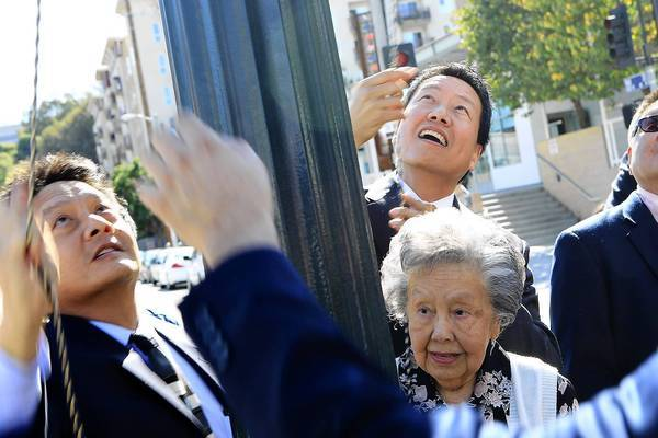 Dolores Wong, right, widow of Judge Delbert E. Wong, and sons Kent, right, and Marshall, left, pull down a velvet cloth to unveil a sign naming the Chinatown intersection of Ord and Hill streets for the former jurist.