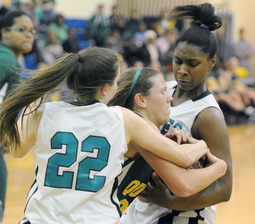 Patterson Mill's Lydia Moro, left, and Maya Peguero battle with Queen Anne's Paige Bryce for the rebound during Friday night's Class 2A East Region girls basketball championship at Patterson Mill. The Huskies won, 64-28.