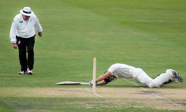 New Zealand's BJ Watling slides in safely in front of umpire Derek Walker on the last day of the four day warm-up international cricket match between New Zealand XI and England in Queenstown on March 2, 2013.