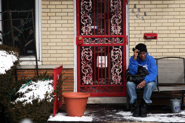 A family member of William Strickland, 72, who was shot and killed as he left his home for dialysis treatment early this morning, sits outside the victim's home on Saturday.