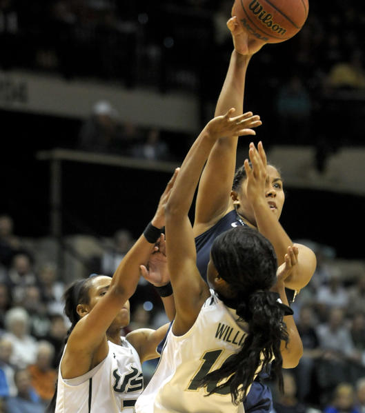 Kaleena Mosqueda-Lewis passes the ball despite tight defense by USF defenders on Saturday afternoon in Tampa. Mosqueda-Lewis led the way for the UConn women with 32 career-high points to lead the Huskies over the University of South Florida Bulls 85-51 at the Sun Dome in Tampa.