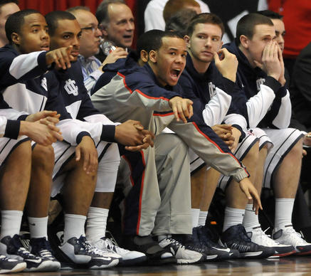 Connecticut Huskies guard Shabazz Napier (13) shouts directions to his teammates from the bench against Cincinnati during the first half at the Fifth Third Arena in Cincinnati, OH, Saturday afternoon. Napier did not play due to an injury to his right foot but UConn led 29-24 at the half.