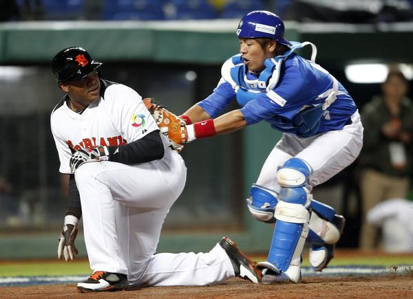 The Netherlands' Andruw Jones is tagged out by South Korea's catcher Kang Minho after he slides in during the fourth inning.