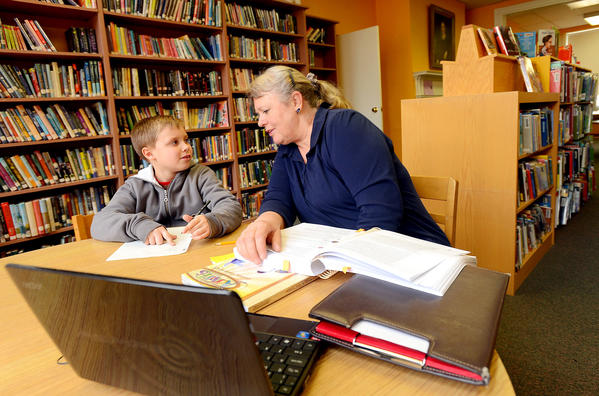 Jacob Short, 8, left, works on his spelling homework with family friend Lesley Kotlanger Thursday afternoon at The Alexander Hamilton Memorial Free Library on E. Main Street in Waynesboro.