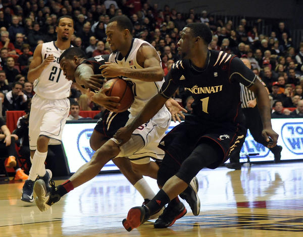 UConn guard Ryan Boatright gets tied up by Cincinnati guard Sean Kilpatrick. Cincinnati guard Cashmere Wright is at right. Boatright led all scorers with 22 points but turned the ball over five times in a 61-56 loss. Kilpatrick scored 20 for the Bearcats.
