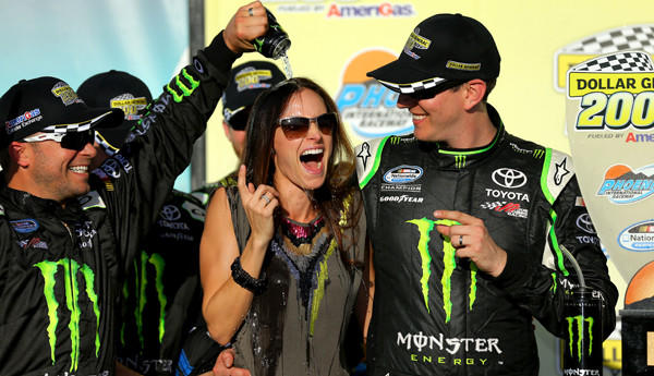Nationwide driver Kyle Busch watches as his wife gets showered with Monster Energy drink during the celebration in Victory Lane on Saturday.
