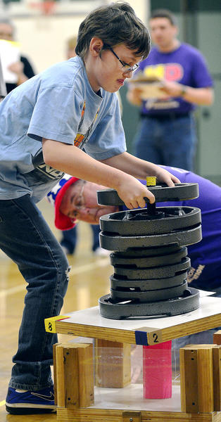 Hayden Thompson, 11, from Northern Middle School places weights totaling 170 pounds on team Rainbow Zebras' structure Saturday during the Western Maryland Regional DestiNation Imagination Tournament at South Hagerstown High School.