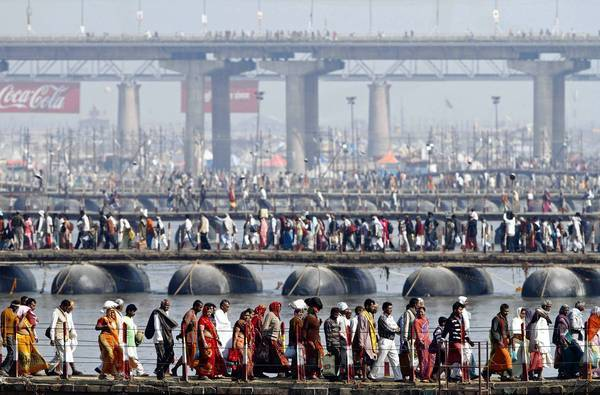 Indian Hindu devotees walk across pontoon bridges at the confluence of the Ganges and Yamuna rivers with the mythical Saraswati on Maghi Purnima, or the full-moon day, considered an auspicious day for bathing.
