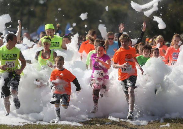 "Runners participate in 2013 Foam Fest 5k at Forever Florida in St. Cloud, Florida Saturday, Feb. 16, 2013. The event bills itself as the ""only obstacle mud race that doubles as a human car wash."""