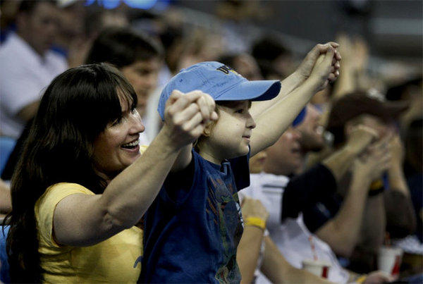 Annie Hughes cheers with her son, Jeffrey Hughes Jr., 9, who is battling cancer, after a Bruins basket during the UCLA-Arizona game.
