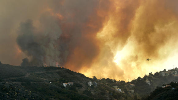 A helicopter flies toward a massive smoke plume rising from a wildfire in Malibu's Latigo Canyon in November.
