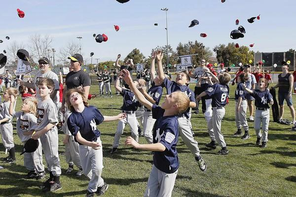 Members of the New York Yankees Minor B team, along with the rest of the league, toss their hats in the air to kick off the beginning of the season during the opening day for the Costa Mesa American Little League.