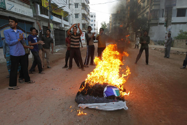 Activists from Bangladesh's Jamaat-e-Islami set fire to a pile of cotton material on a street during the first day of a two-day-long strike to protest against the decision by the country's war crimes tribunal to deliver judgement in the cases involving their top leaders.